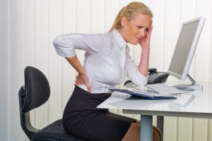 Eine Frau mit Rückenschmerzen vom langen Sitzen im Büro. Gesundheit und Vorsorge am Arbeitsplatz.